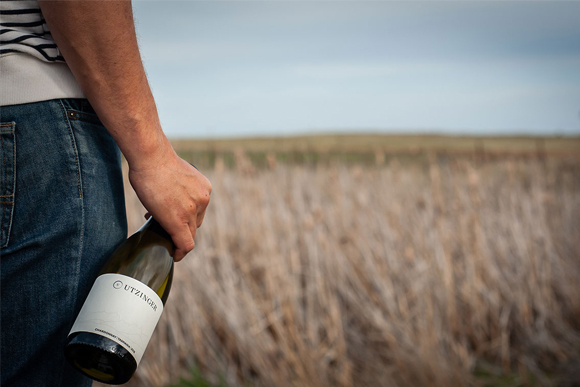 Man holding Utzinger Wine bottle looking out onto field